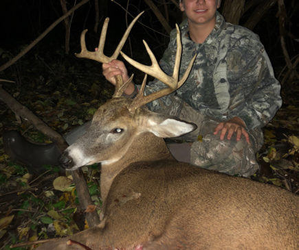 boy posing with buck