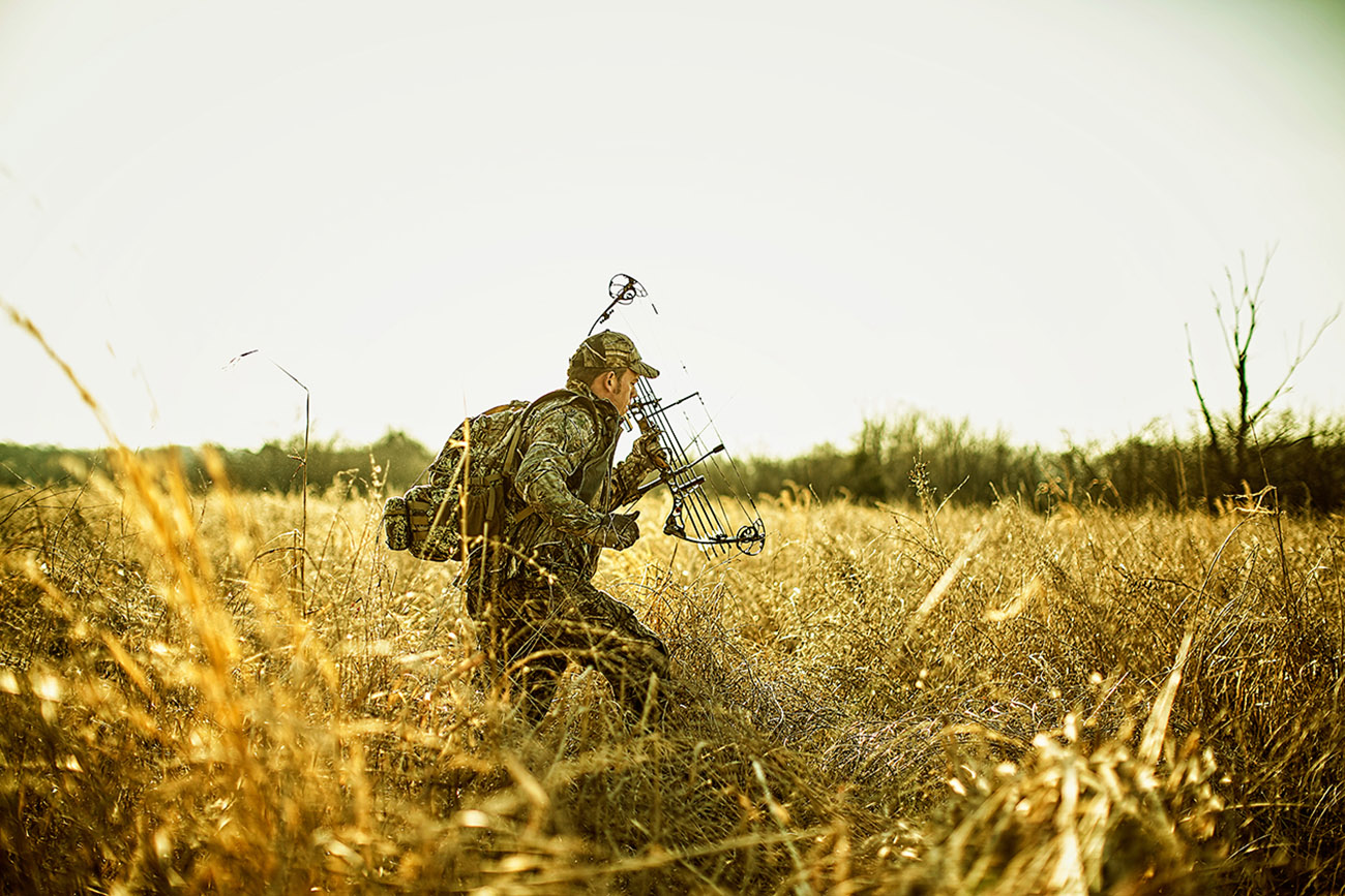 hunter walking through a field with a crossbow