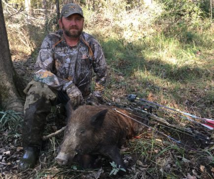 bowhunter posing with hog