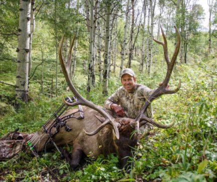 man posing with downed elk