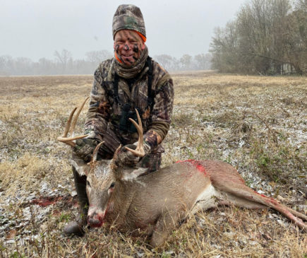 a hunter posing with a downed buck