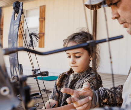 Man showing daughter how to hold a bow